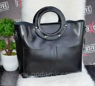 Черная женская кожаная сумка с круглыми ручками.